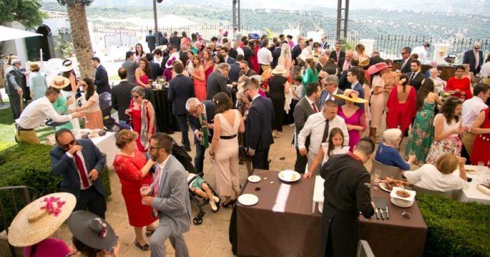 Asistentes a celebración de boda disfrutando de un cóctel en la terraza
