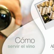 Botellas de vino y mano sirviendo vino